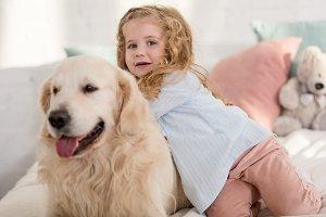 adorable kid and cute dog lying on b