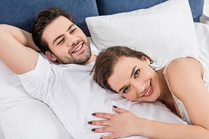 smiling couple cuddling in bed at ho
