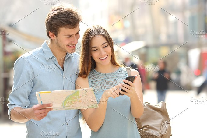 Couple of tourists consulting a city guide and smartphone gps.jpg - People