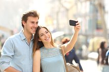 Couple of tourists photographing a selfie in a city street.jpg