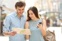 Couple of tourists consulting a city guide and mobile gps.jpg
