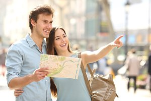 Couple of tourists consulting a city guide searching locations.jpg
