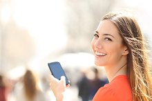 Happy woman walking in the street using a smartphone.jpg