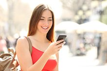 Woman using a smart phone in the street in summer.jpg