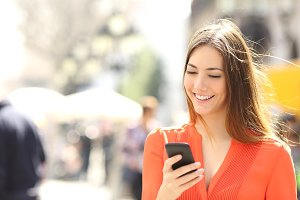 Woman wearing orange shirt texting on the smart phone.jpg