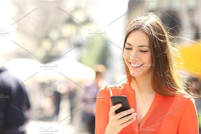 Woman wearing orange shirt texting on the smart phone.jpg - Technology