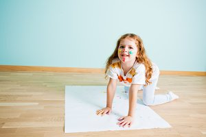 Girl making hand prints on paper on