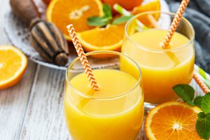 Glasses of juice and orange fruits