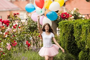Girl with colorful latex balloons in