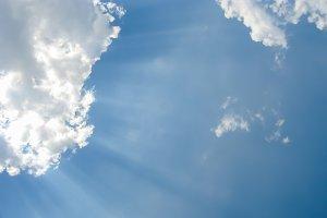 Sunbeams through white clouds