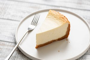 Slice of plain cheesecake on white