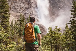 Man walking towards waterfall