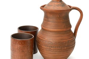 Clay jug and cup isolated on white