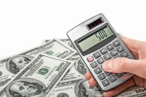 Money and hand holing a calculator