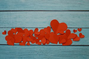Red paper hearts on a blue wooden ba