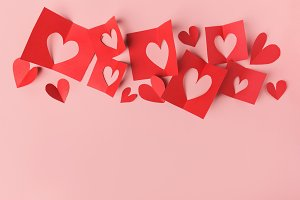 Paper valentines day hearts on pink