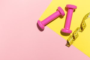 Dumbbells flat lay on pink and yello