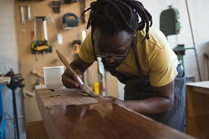 Carpenter painting wooden plank
