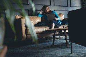 Businesswoman using laptop on a sofa