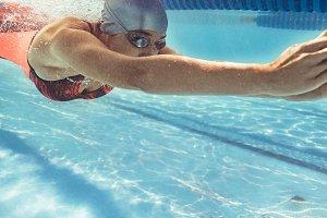 Female swimmer gliding in pool