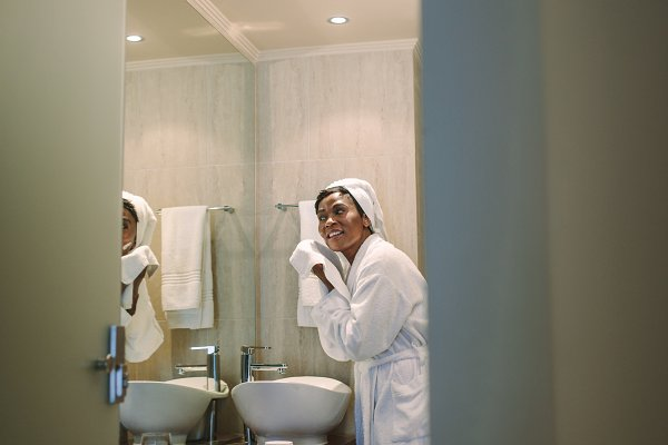Female in bathrobe wiping her face