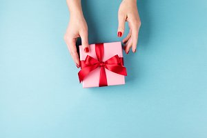 Female hands holding gift box on blu