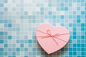 Pink heart gift box on blue mosaic