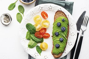 Toasts with avocado on a white plate