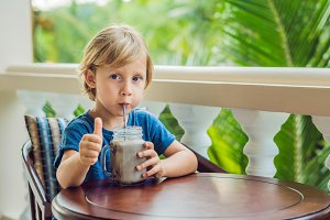 A boy drinks a drink from a carob