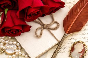 Old letters red rose flowers feather