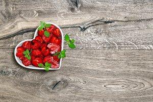 Strawberries heart wooden background