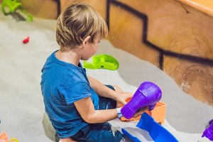 Boy playing with sand in preschool