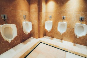 A row of urinals in marble wall