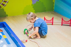 A boy is playing with a toy railroad
