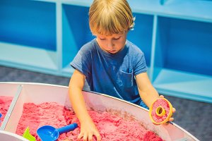 Boy playing with kinetic sand in