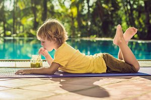 Boy drinking green smoothie lying by