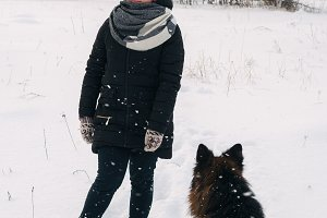 The girl walks with the dog in winte