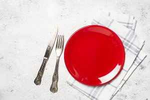 Red plate, cutlery and tablecloth on