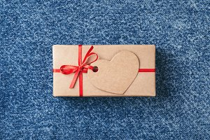 Kraft gift box with red bow and tag.