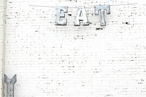 Metal EAT and Lunch signs on brick