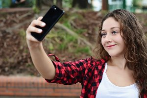 Young woman taking selfie with her s