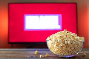 A glass bowl of popcorn and remote