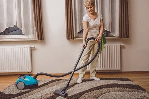 Senior woman vacuuming