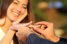 Boyfriend putting a engagement ring in his girlfriend finger.jpg