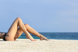 Beautiful woman legs resting on the beach sunbathing.jpg