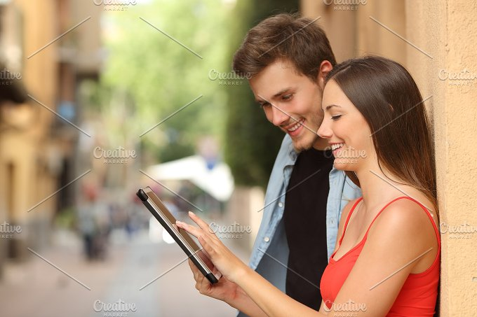 Couple browsing a tablet in the street.jpg - Technology