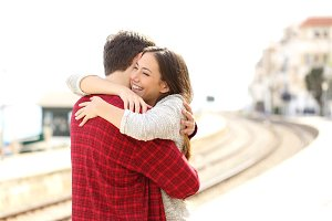 Couple hugging happy in a train station.jpg