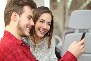 Couple of passengers sharing a smart phone inside a train.jpg