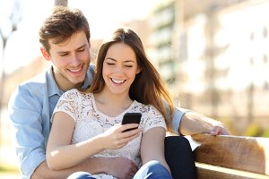 Couple sharing media in a smart phone in a park.jpg
