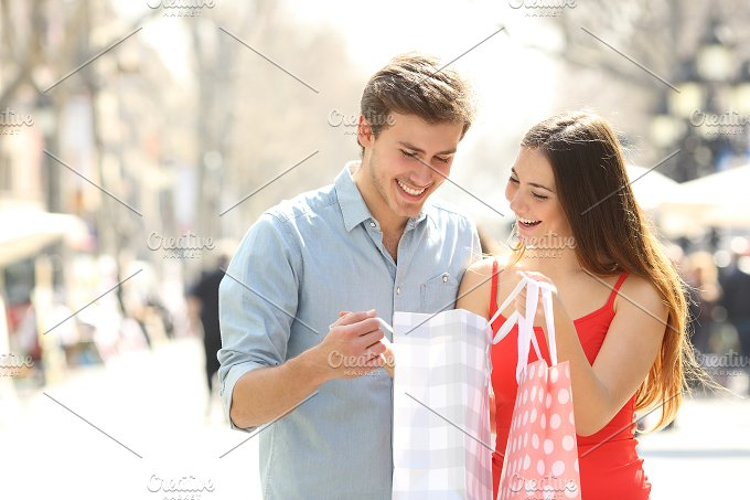 Couple shopping and holding bags in the street.jpg - People